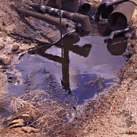 A photo of rusty pipes draining dirty water into a small, muddy puddle